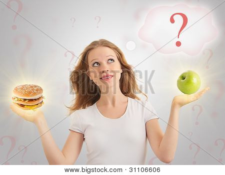 Attractive Girl Makes A Choice Between Healthy And Unhealthy Foods, Apple And Hamburger