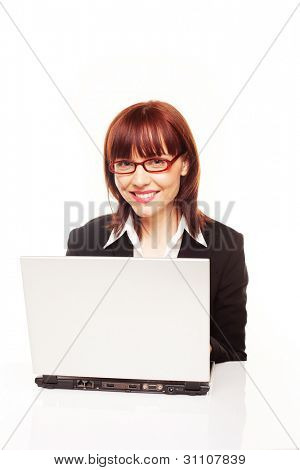 Smiling efficient redhead businesswoman or secretary seated behind her laptop working