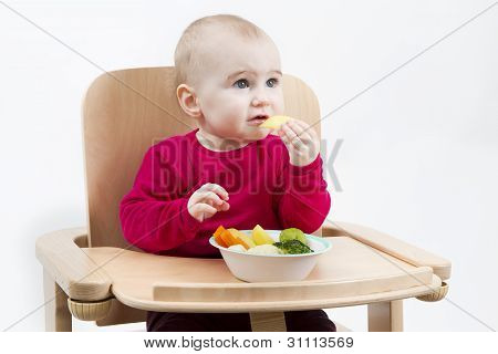 Young Child Eating In High Chair