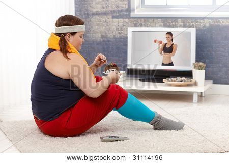 Fat woman sitting on floor with chocolate cake while watching fitness program on television.