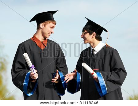 two male graduate students in gown holding diploma over blue sky