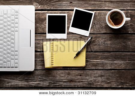 Coffee cup, white laptop keyboard, instant photos and notepad with pen on old wooden table.