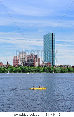Boston Charles River with urban city skyline Hancock building and boat.