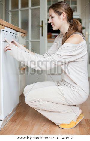 Housework: young woman using a dishwasher