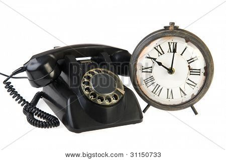vintage black telephone and old analoque clock