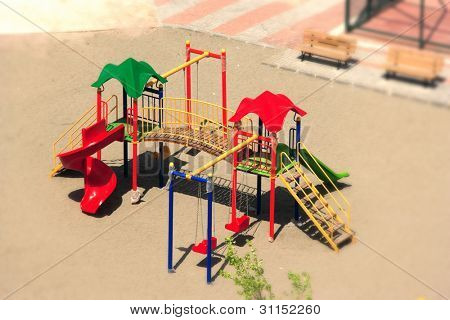 an elevated view of slides and swings in the park