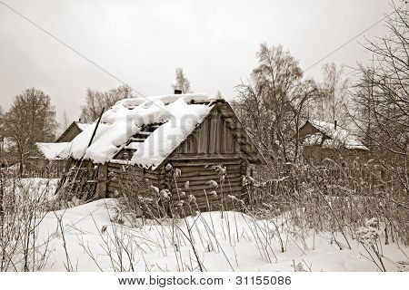 old wooden house amongst winter snow