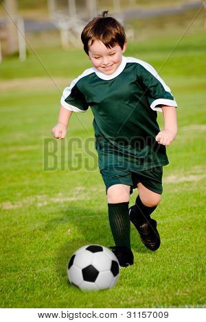 Young boy playing organized soccer in green uniform