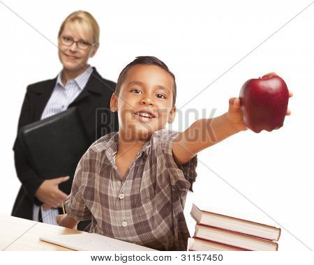 Hispanic Student Boy At Desk with Apple and Female Adult Behind.