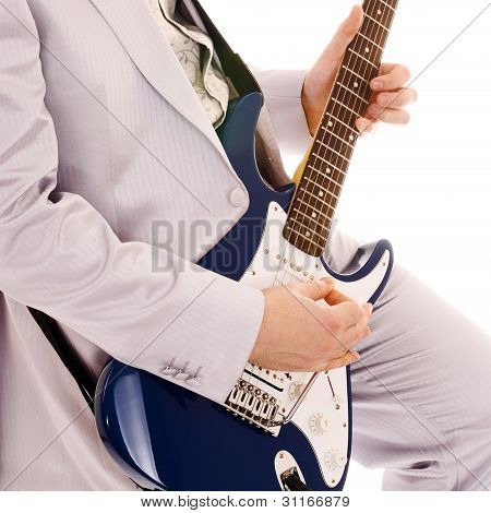 man in white suit playing guitar