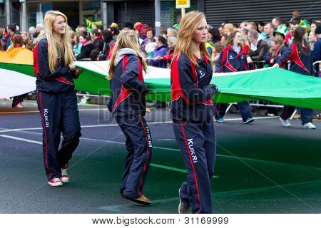 LIMERICK, IRELAND - MARCH 17: Unidentified schoolgirls with Irish flag participate in a parade for St. Patrick's Day. It's a traditional Irish holiday celebration. March 17, 2012 in Limerick, Ireland.