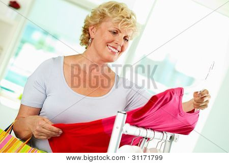 Portrait of middle aged woman choosing new tanktop in clothing department