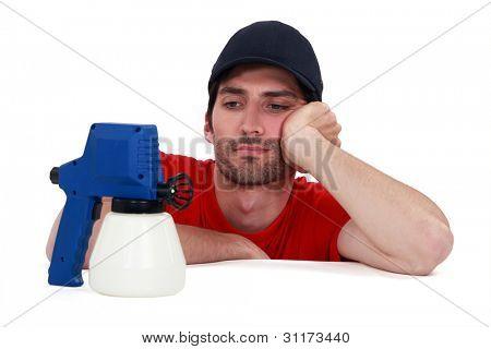 A painter looking a his spray gun.