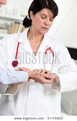 Woman taking a patient's blood pressure