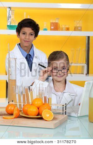 Children doing chemistry experiments with orange juice