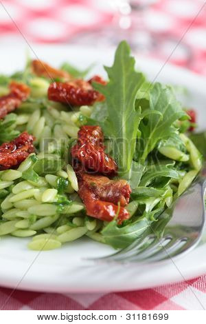 Salad with orzo pasta, rocket, pesto sauce, and sun-dried tomatoes