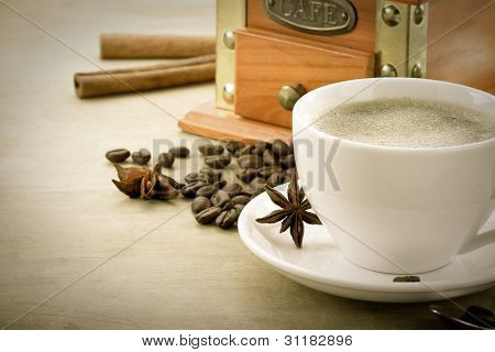 cup full of coffee drink on roasted beans at wooden background