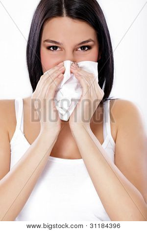 Close up of a young woman sneezing into a tissue