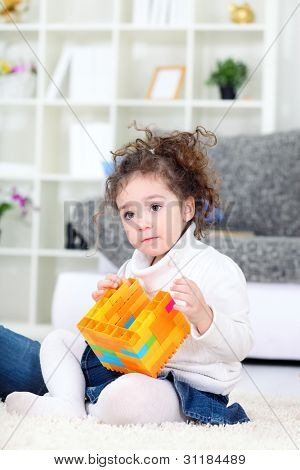 little girl  playing with blocks at home
