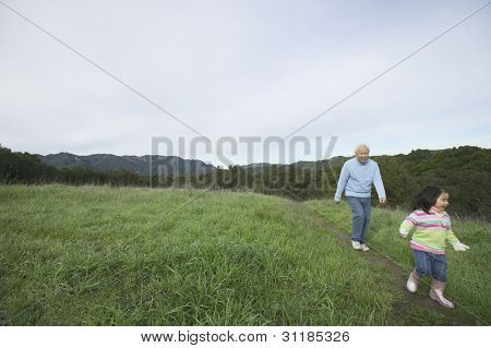 Senior man and granddaughter walking together