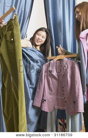 Woman covered with curtain from dressing room looking at clothes
