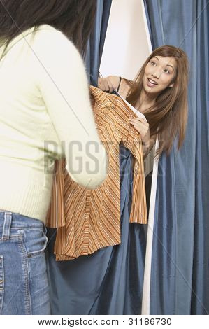 Asian woman peeking out from dressing room