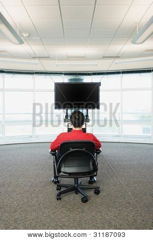 Rear view of man sitting in front of big screen TV