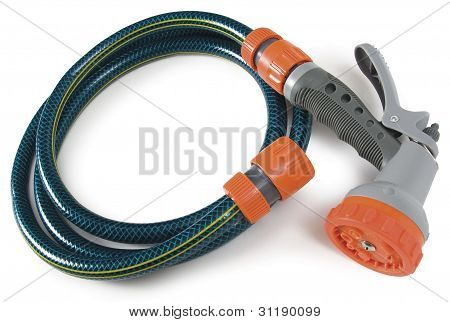 Garden hose and trigger nozzle wound up on white background