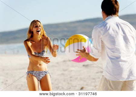 Young couple on a summer beach vacation playing with a beachball and having carefree fun