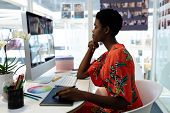 Side view of beautiful young African American female graphic designer using graphic tablet at desk i poster