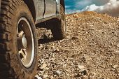 Closeup Photo Of All-terrain Car Wheels In Mountains Area. Off-road 4x4 Car poster