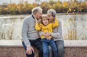 Senior Couple With Baby Grandson In The Autumn Park. Great-grandmother, Great-grandfather And Great- poster