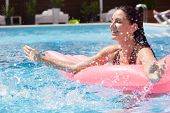 Outdoor Picture Of Relaxed Playful Female Having Fun In Swimming Pool Alone, Lying On Pink Water Mat poster