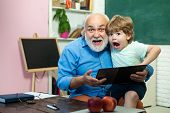 World Teachers Day. Back To School. Happy Cute Grandson And Grandfather Sitting At A Desk Indoors. E poster