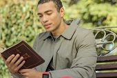 Attentive Short-haired Guy In Grey Coat Reading Bible poster