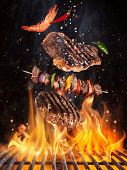Tasty beef steaks and skewers flying above cast iron grate with fire flames. Freeze motion barbecue  poster