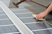 foto of floor heating  - man installing laminate floor over infrared carbon heating system - JPG
