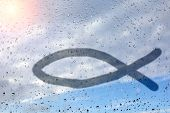 Figure Fish, A Symbol Of Christianity, On Wet Glass. Glass Window With Raindrops Against The Blue Sk poster