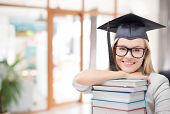 education, graduation and knowledge concept - happy smiling graduate student girl in bachelor hat an poster