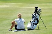 stock photo of foursome  - A fit woman golfer waits for a foursome to put out - JPG