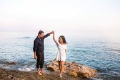 Young Romantic Couple Dancing Ans Smiling At Sunset In The Seaside. Romantic And Honeymoons Concept. poster