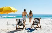 Tropical summer beach holiday couple walk towards the ocean holding hands while on honeymoon vacatio