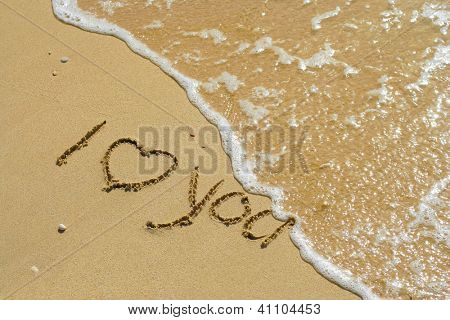 Concept or conceptual hand made or handwritten I love you text with a heart in sand on a beach in an exotic island