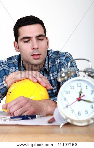 Builder being woken up by alarm clock