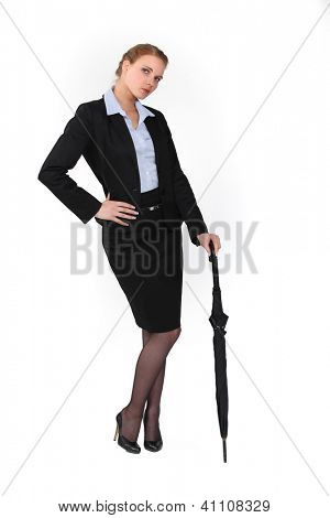 Austere businesswoman holding an umbrella