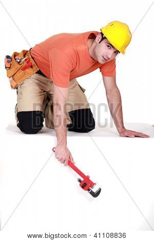Tradesman dangling a pipe wrench from a ledge