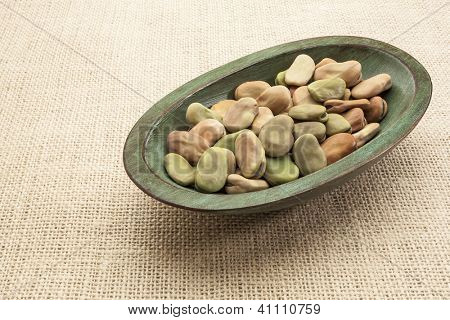 fava (broad) beans  in a rustic wood bowl against burlap canvas