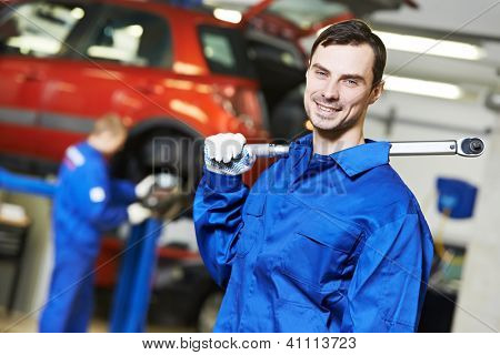 Young repairman auto mechanic inspecting car during automobile maintenance at engine auto repair shop service station