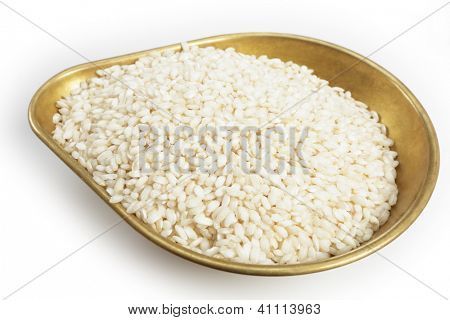 A pile of 460grams (one pound) of arborio Italian rice in the weighing pan from a set of scales, with a light shadow over white.