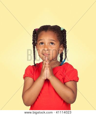 Sad little girl praying for something isolated on a over yellow background
